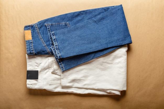 Белые джинсовые брюки синего цвета. ассортимент джинсовой одежды разного цвета в магазине-магазине с пустой этикеткой. белые джинсовые джинсовые брюки, синие джинсы на коричневом столе.