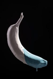 검정색 배경에 바나나 공중 부양에서 흐르는 흰색 파란색 페인트