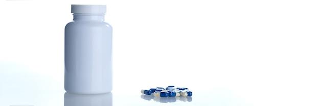 흰색 플라스틱 병의 용기에서 흰색 파란색 알약 캡슐이 유출되었습니다.