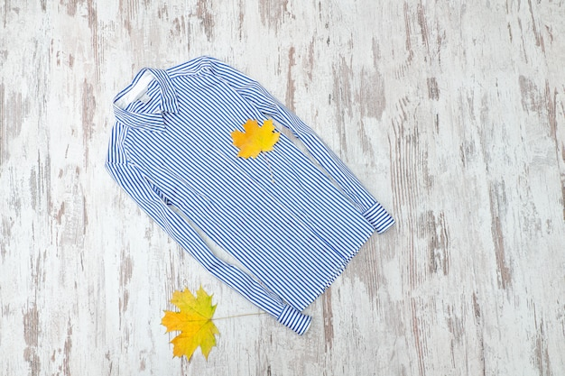 White-blue striped blouse and maple leaves. fashionable concept.