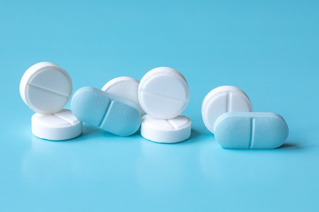 White and blue tablets or pills or medication or drugs