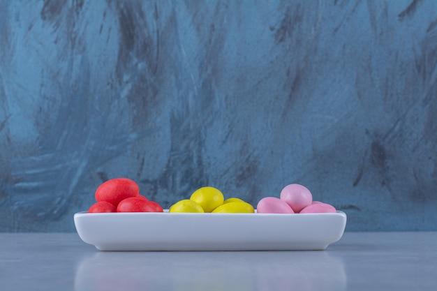 Una lavagna bianca piena di caramelle colorate di fagioli sul tavolo grigio.