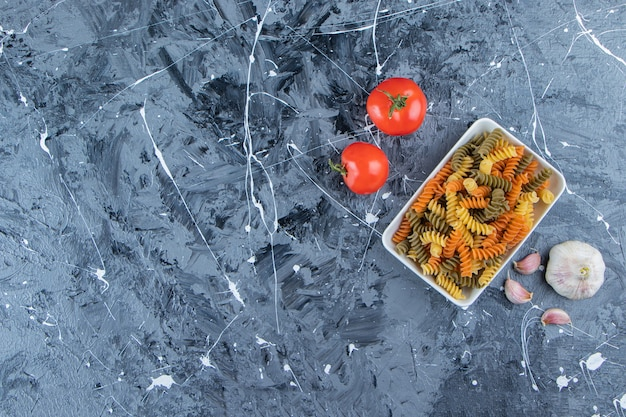 A white board of multi colored macaroni with fresh red tomatoes and garlic on a marble background .