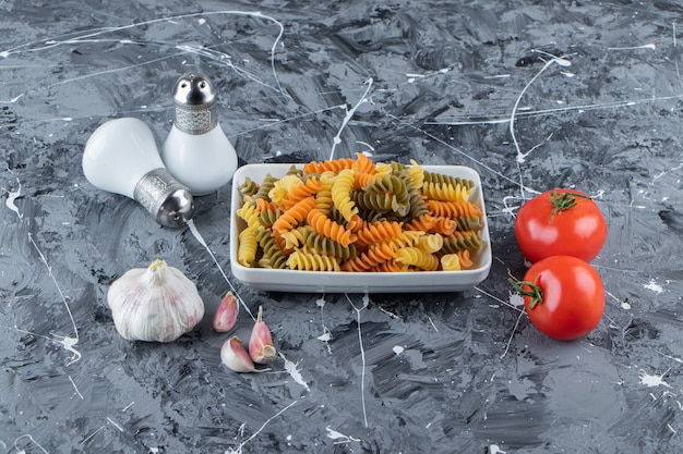 A white board of multi colored macaroni with fresh red tomatoes and garlic on a marble surface .