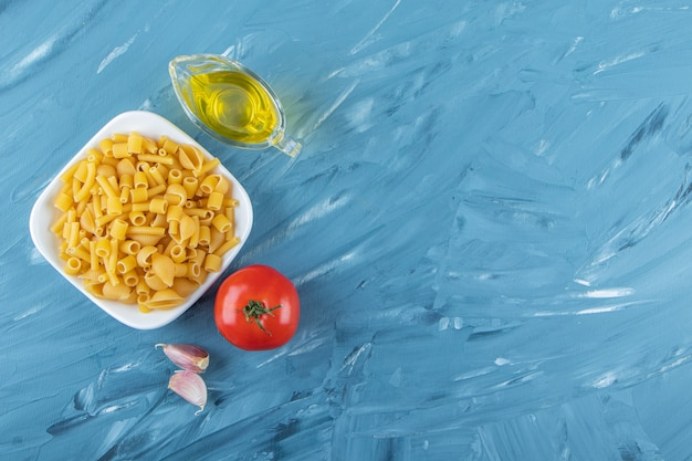 A white board of raw pasta with oil and fresh red tomatoes on a blue background.