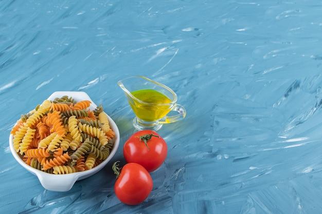 Una lavagna bianca di pasta cruda con olio e pomodori rossi freschi su sfondo blu.