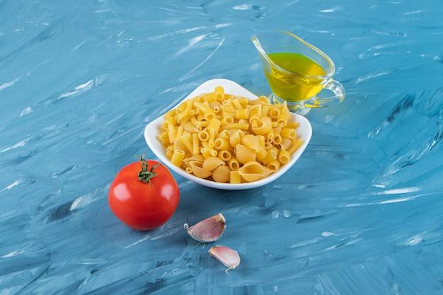 Un bordo bianco di pasta cruda con olio e pomodori rossi freschi su una superficie blu.