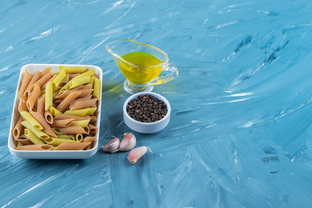 A white board of raw pasta with oil and pepper corns on a blue background.