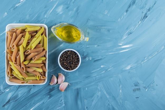 Una lavagna bianca di pasta cruda con olio e pepe in grani su sfondo blu.