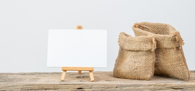 White board stand and two different size burlap bags on grunge wooden  shelf with copy space isolated over white background