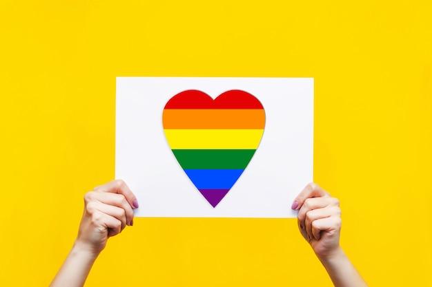 랠리 회의 항의 관용 개념에 대 한 밝은 색 노란색 벽에 고립 된 여성 손에 심장 모양의 lgbt 플래그 디자인 화이트 보드