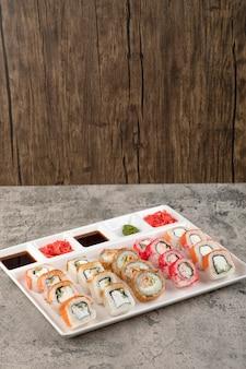 Una lavagna bianca con diversi tipi di deliziosi involtini di sushi su un tavolo di pietra