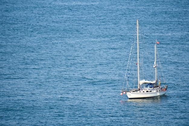 Белая лодка плывет по мирному морю днем
