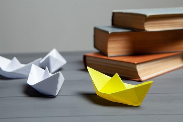白いボートは、灰色の背景の本の隣にある黄色に行きます