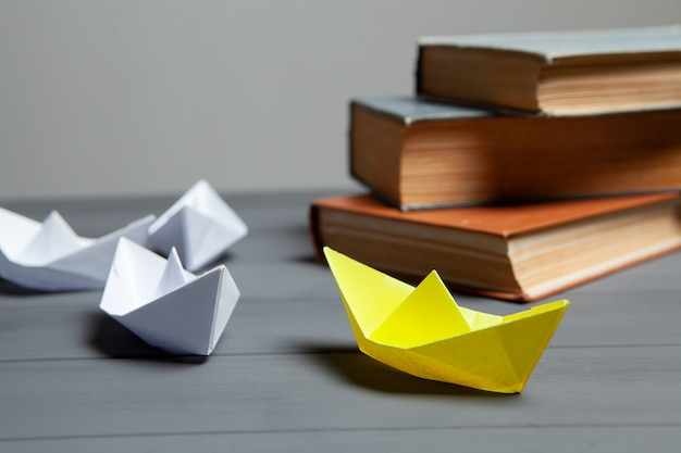 White boats go for yellow next to books on a gray background