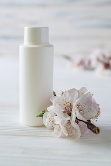White body care cosmetics bottle with flowers close up