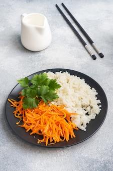 흰 밥과 매운 한국 당근 샐러드를 접시에 담았습니다.