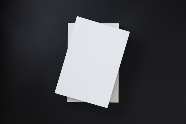 White book covers stacked on a black background