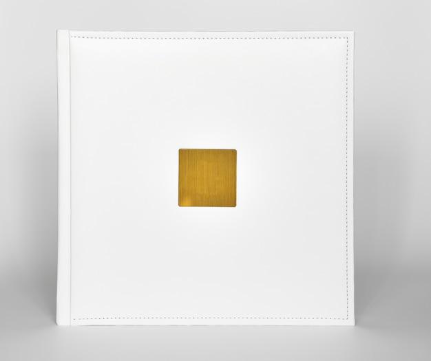 Белая книга в кожаном переплете с золотой металлической вставкой для надписи. полиграфическая продукция. фотоальбомы и альбомы. отдельные продукты.