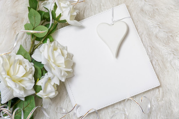 White book with bouquet of roses and white heart background