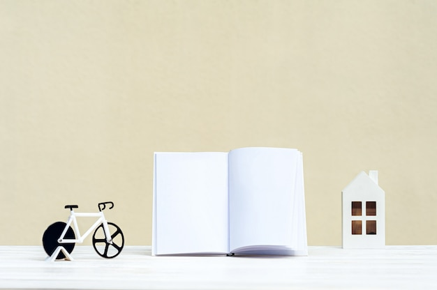 White book on a wooden tabletop, next is a mini house with a bicycle.