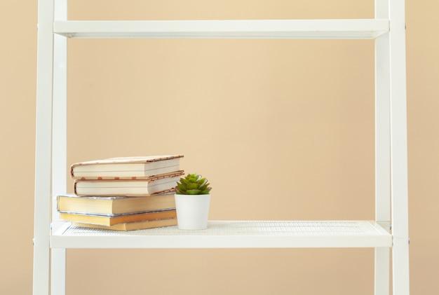 Белая книжная полка с книгами и канцелярскими принадлежностями на бежевой стене
