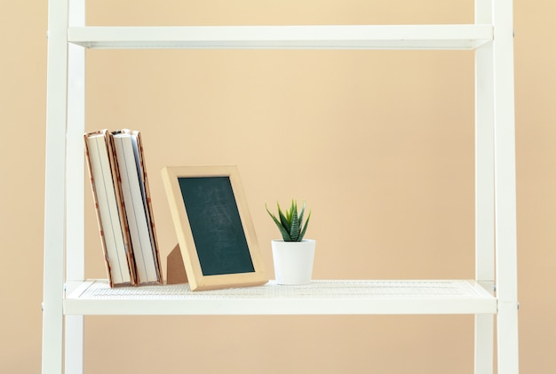 White bookshelf with  books and stationery against beige wall