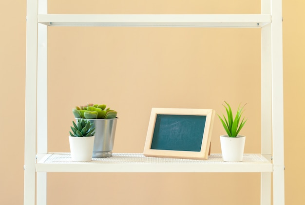 White bookshelf with plant in pot against beige background