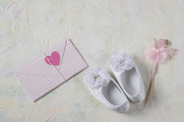 White booties made of lace for a girl and envelope with a pink heart