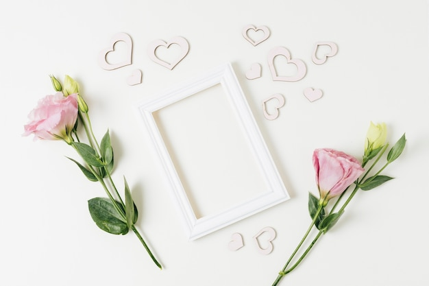 White border frame with heart shapes and eustoma flowers on white backdrop