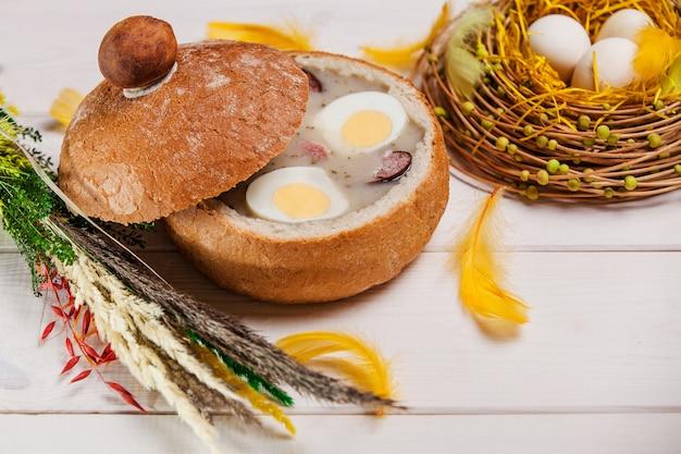 Белый борщ в хлебе на деревянном столе