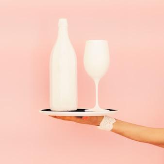 Белая бутылка и стакан на подносе. модный дизайн