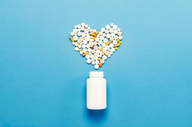 Белая бутылка и разноцветные таблетки в форме сердца. синий фон понятие о лекарственных средствах, лекарственных средствах, препаратах для лечения сердечно-сосудистых заболеваний. медицинская помощь. плоская планировка, вид сверху