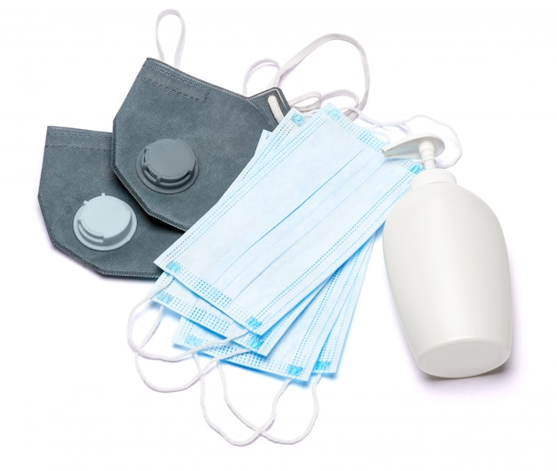 White bottle of cream, lotion, sanitizer or liquid soap and protective mask isolated on white background