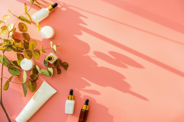 ホワイトボトルクリーム、美容製品ブランドのモックアップ。ピンクのトップビュー。