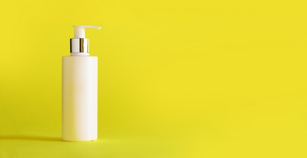 White bottle of moisturizing lotion on yellow background with copy space