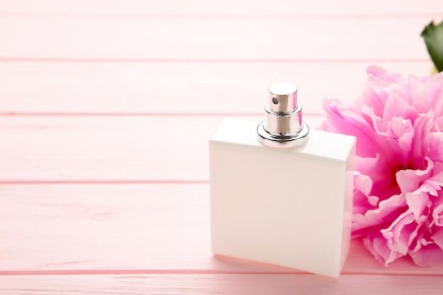 분홍색 배경에 분홍색 꽃과 향수의 흰색 병