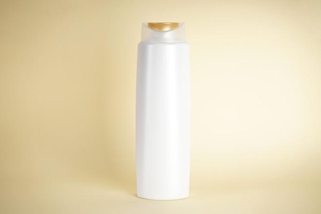 Белая бутылка шампуня на желтом фоне.