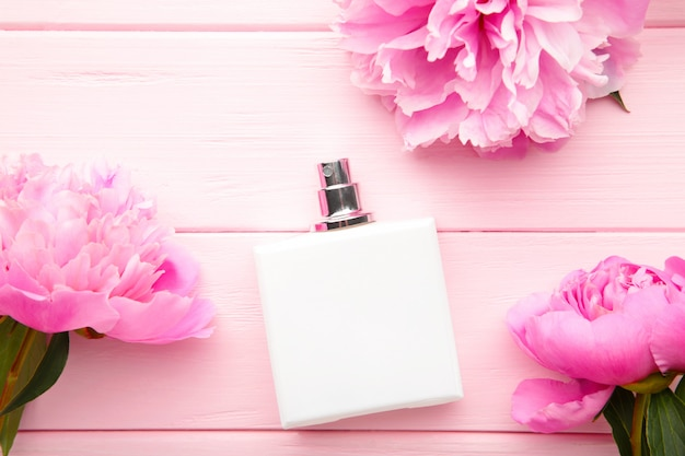 White bottle of perfume with pink flower on pink background