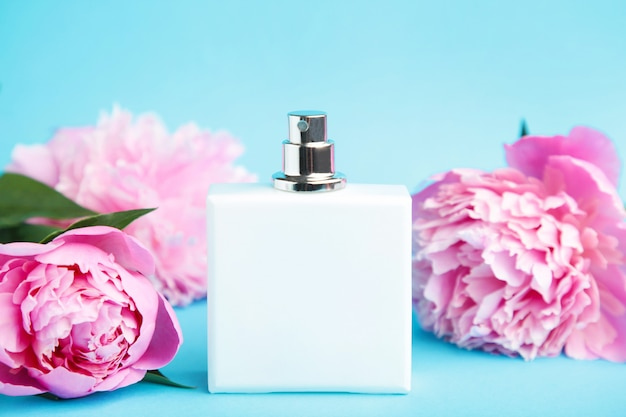 White bottle of perfume with pink flowers on blue background