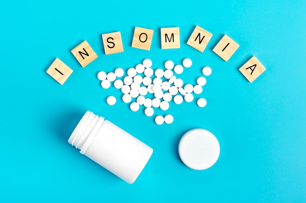 White bottle and pills on a blue background. the concept of  treatment of insomnia.