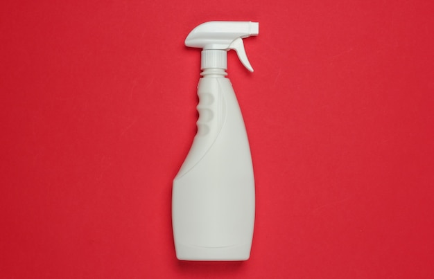 White bottle of spray for cleaning on red background. top view. minimalism