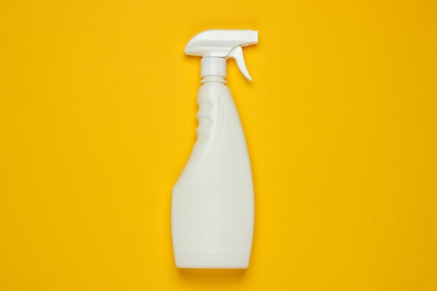 White bottle of spray for cleaning on yellow background. top view. minimalism