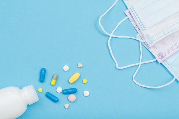 青い背景にさまざまな錠剤とイヤループフェイスマスクが付いた白いボトル。上面図