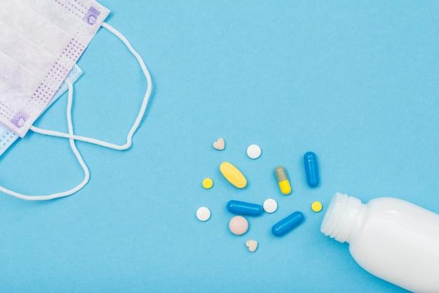 コピースペースのある青い背景にさまざまな錠剤とイヤループフェイスマスクが付いた白いボトル。上面図