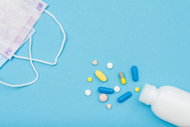 White bottle with different pills and earloop face masks on blue background with copy space. top view