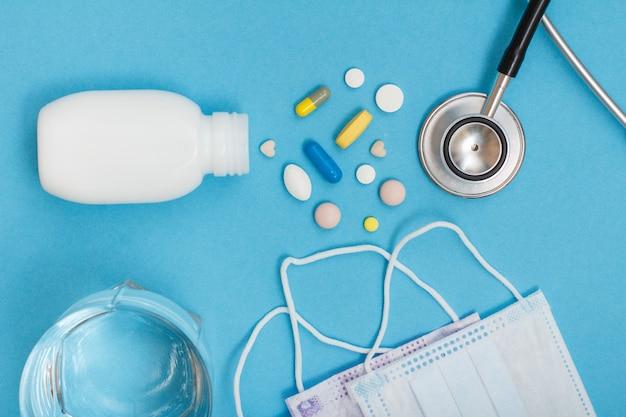 さまざまな錠剤、電話内視鏡、イヤーループフェイスマスク、青い背景に水のガラスが入った白いボトル。上面図