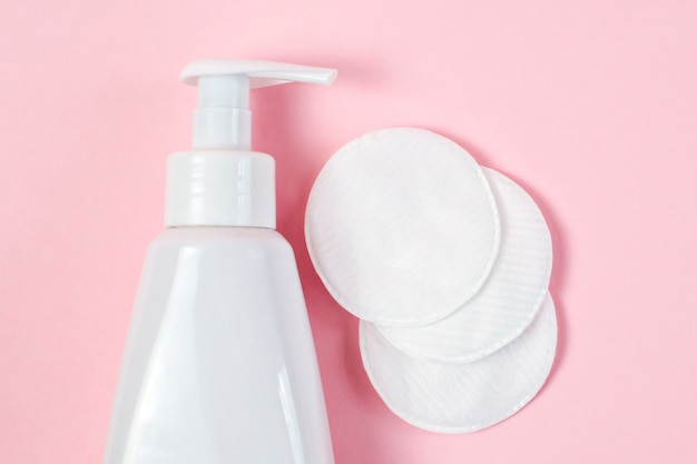 얼굴을 씻고 닦을 수있는 젤이 들어있는 흰색 병, 부드러운면 패드, 메이크업 제거를위한 미셀 워터, 피부 클렌징 및 파스텔 핑크 테이블의 미용 트리트먼트.