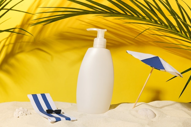 White bottle with shampoo or shower gel on summer travel background with paper umbrella, sunglasses and green palm leaves. moisturizing sunscreen for sensitive skin and body lotion