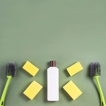 White bottle with sponge and brush on green background